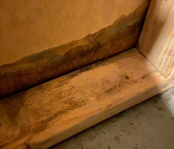 image of baseboard area in a severely flooded basement showing visible water damage