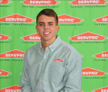 image of male sitting in front of SERVPRO backdrop