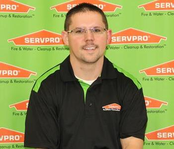 male employee sitting in front of servpro backdrop