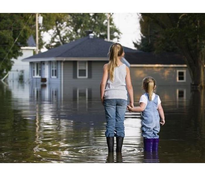 image of two young girls standing outside in a flash flood with severe water in the streets