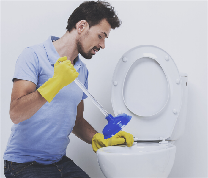 man plunging his clogged toilet